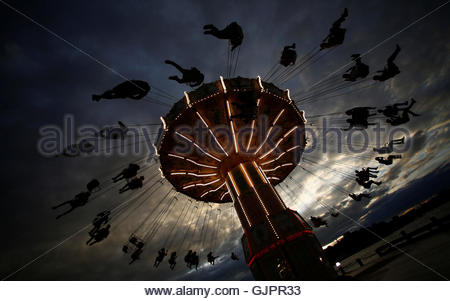 People ride on a merry-go-round carousel during sunset in Stockholm, Sweden, August 16, 2016. Picture taken August - Stock Photo
