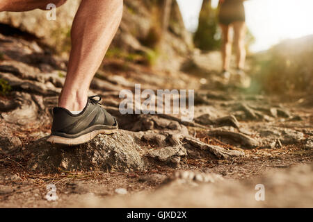 Closeup of man trail running on rocky terrain. Low section of male runner on cross country run. - Stock Photo