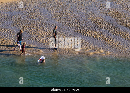 Holidaymakers enjoy a late evening stroll along the Gannel Estuary on Crantock Beach in Newquay; Cornwall. - Stock Photo
