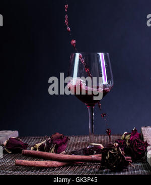 splash of red wine in to a glass - Stockfoto