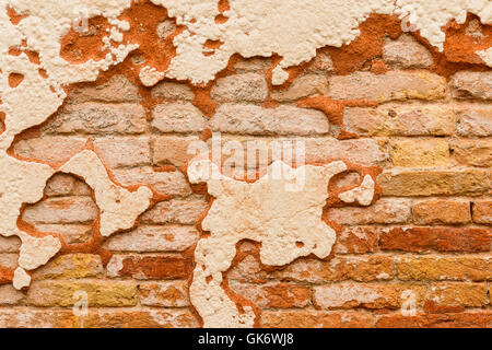 Close up of old brick wall with broken plaster - Stock Photo
