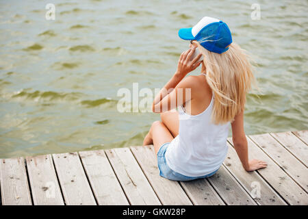 Young blonde woman sitting on the bridge and talking on phone - Stockfoto