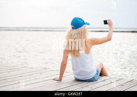 Young blonde girl taking selfie with phone while sitting on the wooden pier - Stock Photo