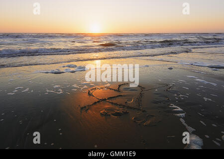 Figure heart pierced by an arrow drawn on the sandy beach lapped by the waves. - Stockfoto
