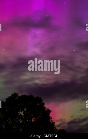 A power aurora turned the sky purple and green above shattered clouds. - Stock Photo