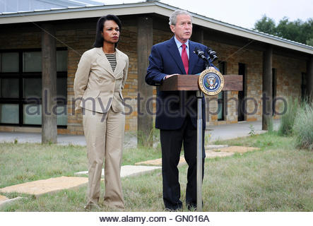 US President George W. Bush (R) stands with US Secretary of State Condoleezza Rice as he comments on the situation - Stock Photo