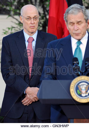 US Treasury Secretary Henry Paulson (L) stands with US President George W. Bush (R) as he makes a statement in the - Stock Photo
