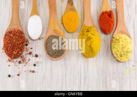 Various spices in wooden spoons on a wooden table - Stock Photo