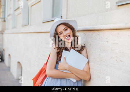 Cheerful pretty young woman in hat with blank covered magazines winking and showing thumbs up - Stock Photo