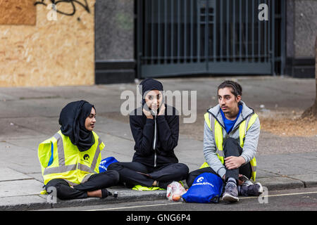 Three people sitting on the pavement at the Notting Hill carnival in West London waiting for the crowds to arrive - Stockfoto