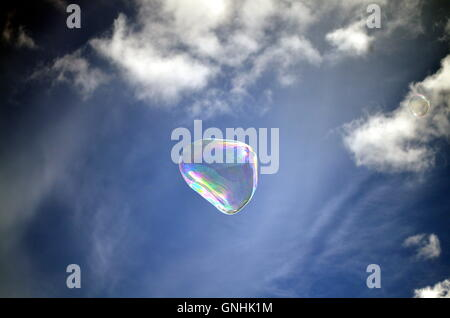 Soap rainbow bubble on blue sky background - Stock Photo