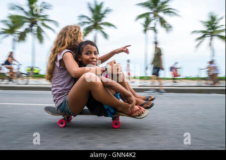 RIO DE JANEIRO - MARCH 06, 2016: Young Brazilians ride past in motion blur on skateboard on the beachfront Avenida - Stock Photo