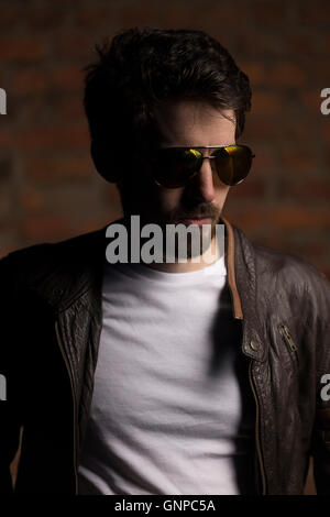 Male model with groomed beard wearing white tee, leather jacket and aviator shades with brick wall backdrop - Stock Photo