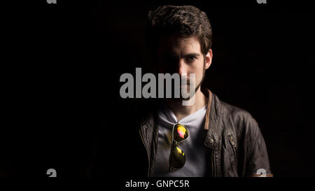 Male model with groomed beard wearing white tee and leather jacket, half in shadow - Stock Photo