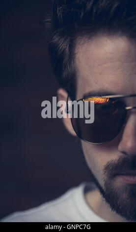 Male model with groomed beard wearing white tee and aviators reflecting red orange yellow sunset light - Stock Photo