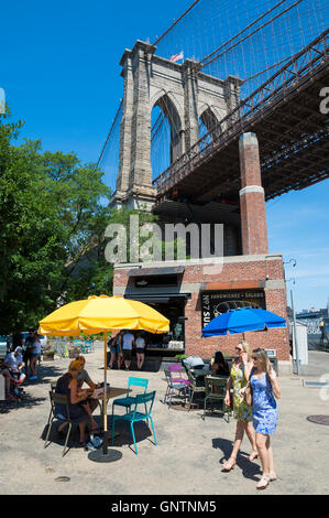 NEW YORK CITY - AUGUST 27, 2016: Tourists gather in the shade under an imposing view of the Brooklyn Bridge on a - Stock Photo