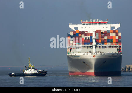 Container ship OOCL Singapore leaving a container terminal in the Port of Antwerp. - Stock Photo