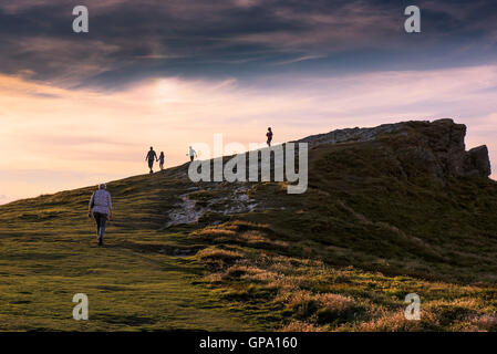 Sunset as holidaymakers enjoy a late evening walk on the summit of Porth Island in Newquay, Cornwall. - Stock Photo