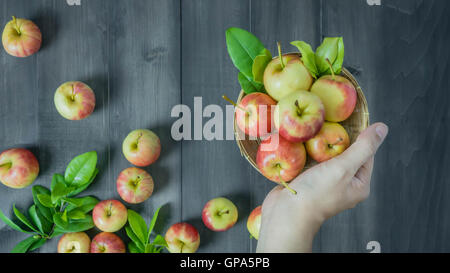 human hand holding red and yellow apple  on wooden background , Top view - Stock Photo