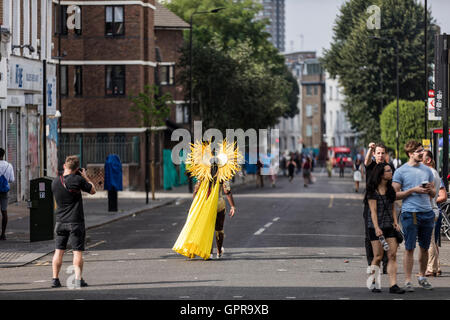Woman wearing yellow costume at the Notting Hill carnival  in the street with people taking photographs - Stock Photo