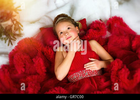 Little winter Princess in a precious crown in red dress lies on artificial snow. Welcomes New year and Christmas - Stock Photo