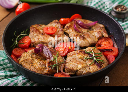 Juicy pork steak with rosemary and tomatoes on pan - Stock Photo