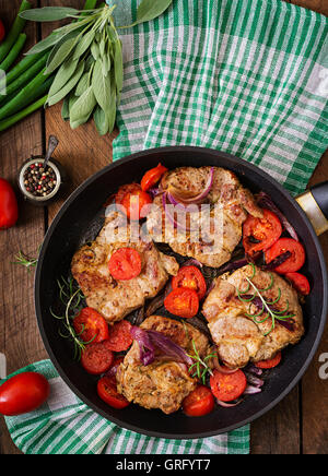 Juicy pork steak with rosemary and tomatoes on pan. Top view - Stock Photo