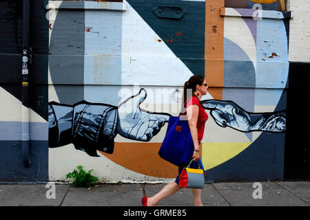 A woman walking pass by a mural along Christopher Columbus Drive in Historic Downtown,Jersey City,New Jersey,USA - Stock Photo