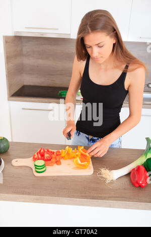 long-haired young woman prepares a modern, stylish kitchen healthy vegetable salad - Stock Photo