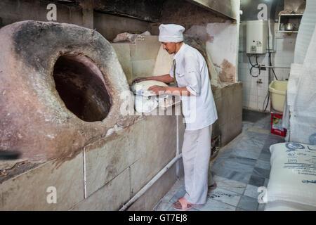 A baker uses a tandoori oven to bake fresh taftoon bread in Yazd, Iran. - Stock Photo