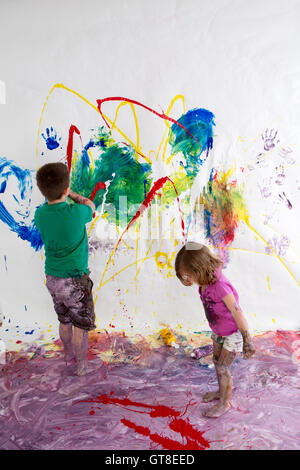 Young brother and sister painting together creating a modern abstract of vivid colors on the wall and floor using - Stock Photo