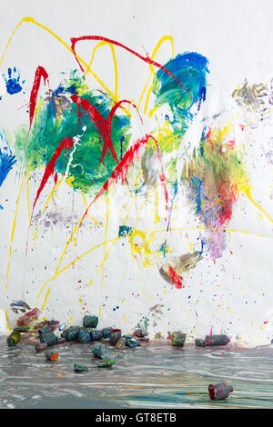 Scattered paint tins below a modern abstract artwork in bright vivid colors painted on a white wall in an expression - Stock Photo