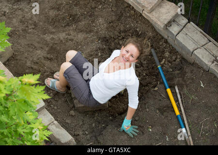 Attractive middle-aged female gardener working in her backyard doing maintenance on the flowerbeds sitting on the - Stock Photo
