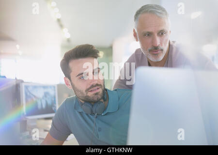 Creative businessmen working at computer in office - Stock Photo