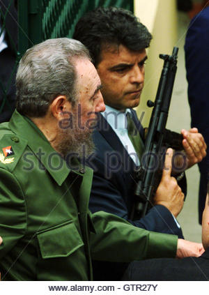 Cuban President Fidel Castro (L) walks past a Federal Police officer armed with an MP-5 machine gun after visiting - Stock Photo