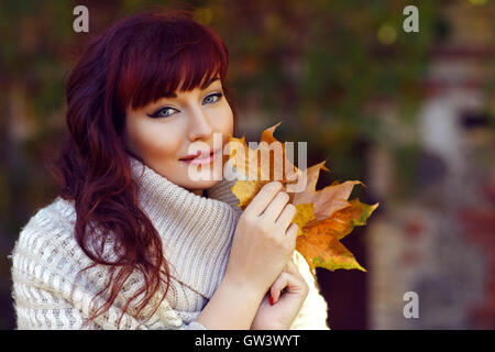 Beautiful girl outdoors with autumn leaves - Stock Photo