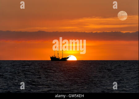 Pirate ship fantasy is an old wooden pirate ship with full flags as the sun sets on the ocean horizon in a colorful - Stock Photo