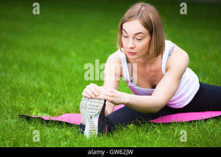 Young beautiful woman is stretching in the park. - Stock Photo