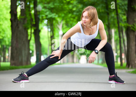 Young beautiful woman stretching in the park. - Stock Photo