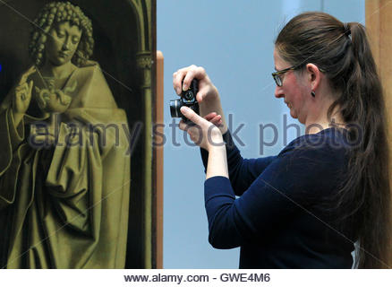 A restorer takes a picture one of the 24 framed panels of the Altarpiece or Adoration of the Mystic Lamb at The - Stock Photo