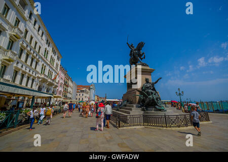 VENICE, ITALY - JUNE 18, 2015: Sculpture in the middle of a nice street in Venice, on the side a hotel with a nice - Stock Photo