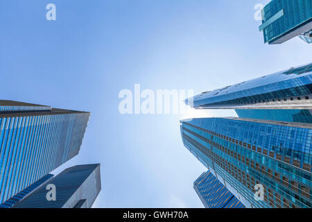 Abstract up view of skyscrapers with blue sky in Singapore downtown. Business and finance headquarters. Sun reflecting - Stock Photo