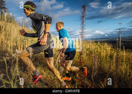 two men runners skyrunners running uphill trail in grass on blue sky background during marathon Vertical kilometer - Stock Photo