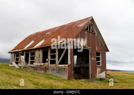Run down old shed clad in rusty corrugated iron, situated on the coast - Stock Photo