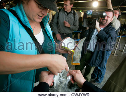 A passenger repacks hand cream from a can into a plastic bag prior to the security check at Frankfurt's airport, - Stock Photo