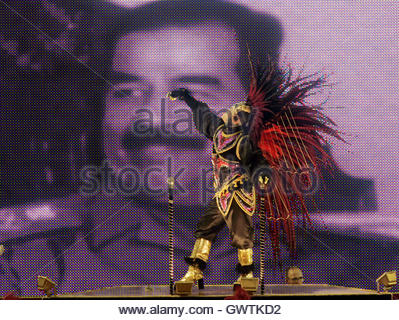 A reveler of the Mocidade samba school performs on the top of a carnival float with an image of former Iraq president - Stock Photo