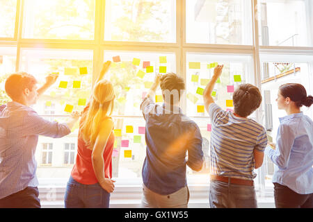 Students putting sticky notes on window for planning analysis - Stockfoto