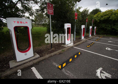 electric car charging station with a tesla sedan plugged in tesla stock photo royalty free. Black Bedroom Furniture Sets. Home Design Ideas