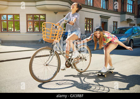 Laughing trendy young woman on a skateboard being towed along an urban street by her friend riding a bicycle - Stock Photo