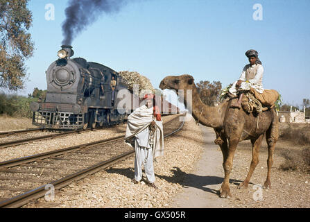 A wondering tribesman from north Pakistan waits for a British inside-cylinder 0-6-0 to pass with a heavy train, - Stock Photo